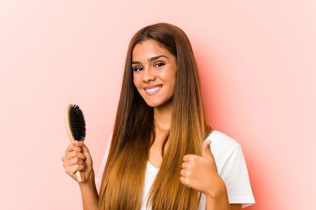 Giovane donna caucasica che tiene una spazzola per capelli sorridente e alzando il pollice
