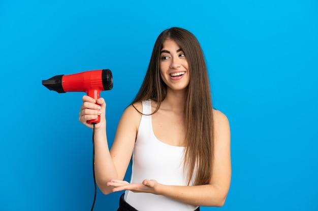 Giovane donna caucasica con in mano un asciugacapelli isolato su sfondo blu che allunga le mani di lato per invitare a venire