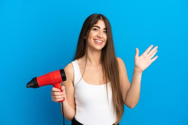 Giovane donna caucasica che tiene un asciugacapelli isolato su sfondo blu salutando con la mano con espressione felice
