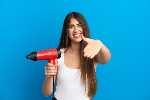 Giovane donna caucasica con in mano un asciugacapelli isolato su sfondo blu che stringe la mano per aver chiuso un buon affare