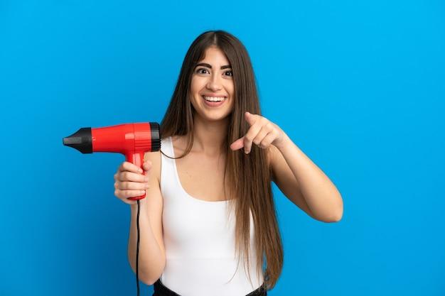 Giovane donna caucasica con in mano un asciugacapelli isolato su sfondo blu sorpreso e rivolto verso la parte anteriore