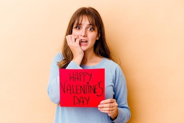 La giovane donna caucasica che tiene un felice giorno di san valentino ha isolato le unghie mordaci, nervose e molto ansiose.