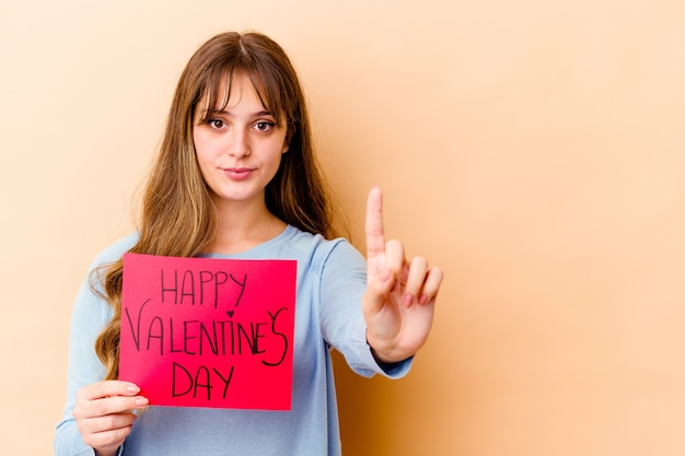 La giovane donna caucasica che tiene un giorno di san valentino felice ha isolato la mostra numero uno con il dito.