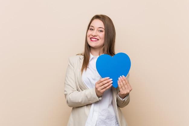 Giovane donna caucasica che tiene un'icona del cuore