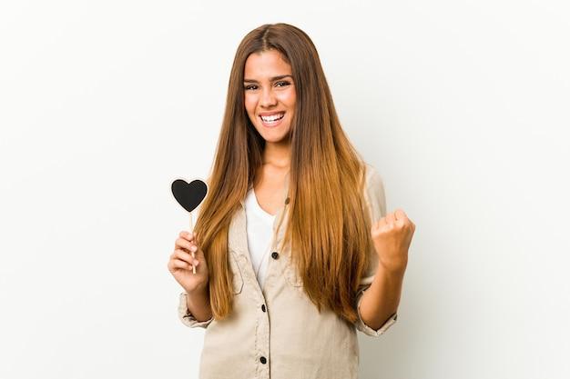 Giovane donna caucasica che tiene una figura del cuore che incoraggia spensierata ed eccitata. concetto di vittoria.