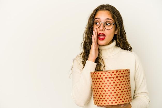 La giovane donna caucasica che tiene una scatola di san valentino del cuore isolata sta dicendo una notizia di frenata calda segreta e sta guardando da parte