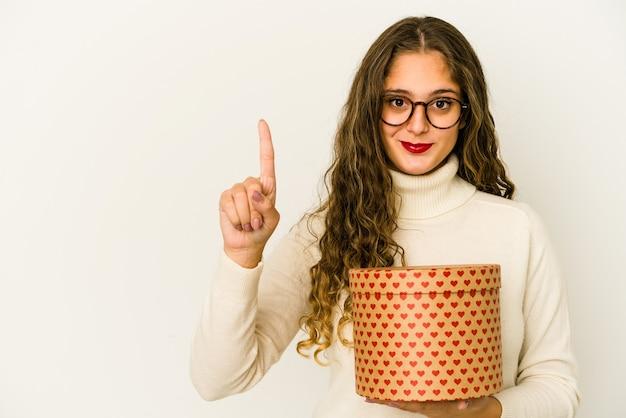 Giovane donna caucasica che tiene una casella di giorno di biglietti di s. valentino del cuore isolata che mostra il numero uno con il dito.