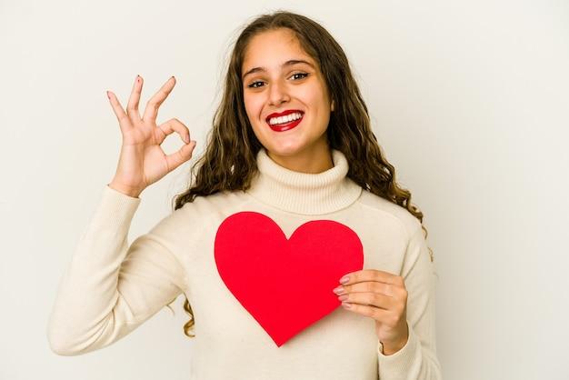 La giovane donna caucasica che tiene una forma di giorno di biglietti di s. valentino del cuore ha isolato il gesto giusto che mostra allegro e sicuro.