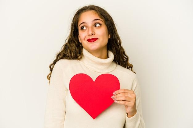 La giovane donna caucasica che tiene una forma di giorno di biglietti di s. valentino del cuore ha isolato il sogno di raggiungere obiettivi e scopi