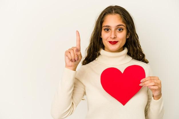 Giovane donna caucasica che tiene una forma di giorno di biglietti di s. valentino del cuore isolata che mostra il numero uno con il dito.