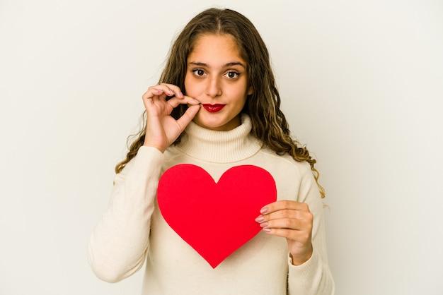 Giovane donna caucasica che tiene una forma di san valentino del cuore isolata con le dita sulle labbra che mantengono un segreto.