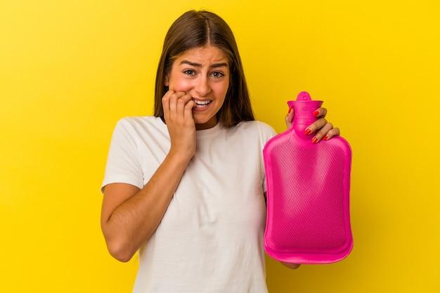 Giovane donna caucasica in possesso di una bottiglia d'acqua calda isolata su sfondo giallo che si morde le unghie, nervosa e molto ansiosa.