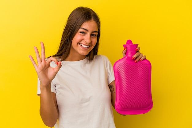Giovane donna caucasica che tiene in mano una bottiglia d'acqua calda isolata su sfondo giallo allegro e fiducioso che mostra gesto ok.