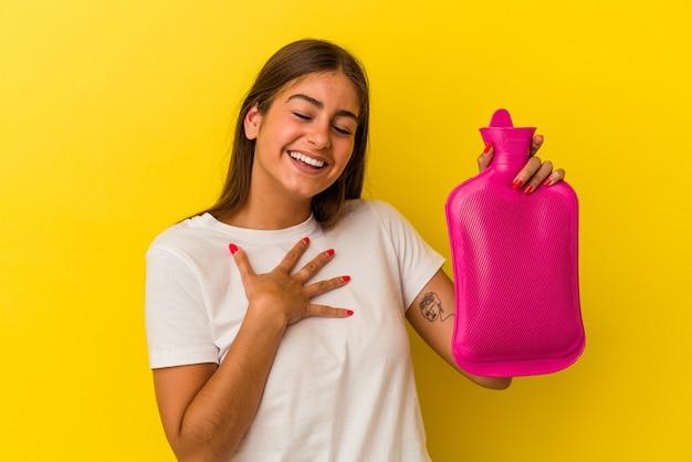 La giovane donna caucasica che tiene una bottiglia d'acqua calda isolata su sfondo giallo ride ad alta voce tenendo la mano sul petto.