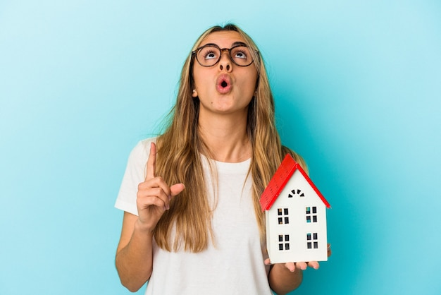 Giovane donna caucasica in possesso di un modello di casa isolato su sfondo blu rivolto verso l'alto con la bocca aperta.