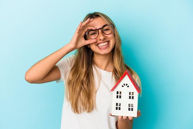 La giovane donna caucasica che tiene un modello della casa isolato sulla parete blu ha eccitato mantenendo il gesto giusto sull'occhio