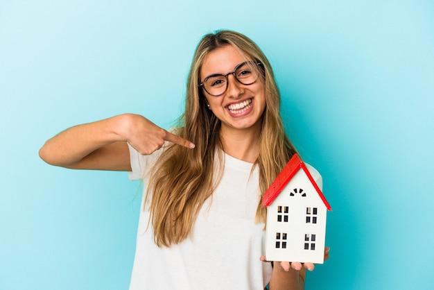 Giovane donna caucasica che tiene un modello di casa isolato sulla persona della parete blu che indica a mano uno spazio della copia della camicia, fiero e sicuro