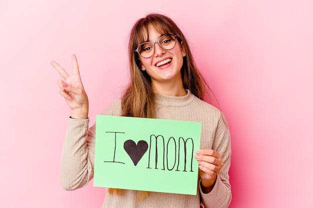 Giovane donna caucasica che tiene una mamma i love isolata gioiosa e spensierata che mostra un simbolo di pace con le dita.