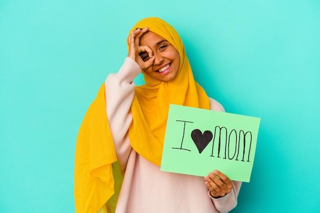 La giovane donna caucasica che tiene un amo la mamma isolata su fondo rosa eccitato mantenendo il gesto giusto sull'occhio.