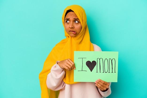 La giovane donna caucasica che tiene una mamma di i love isolata sul muro rosa confusa, si sente dubbiosa e insicura.