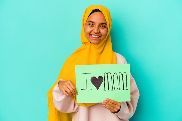 Giovane donna caucasica che tiene una mamma di i love isolata sulla parete rosa felice, sorridente e allegra.