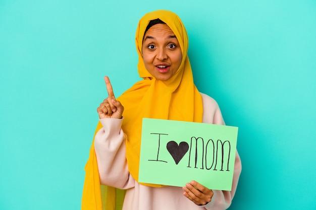 Giovane donna caucasica che tiene una mamma i love isolata sulla parete rosa con una grande idea, il concetto di creatività.
