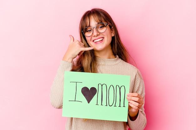 Giovane donna caucasica che tiene una mamma di amore isolata che mostra un gesto di chiamata di telefono cellulare con le dita.