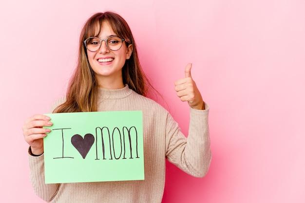 La giovane donna caucasica che tiene una mamma di amore ha isolata sorridendo e alzando il pollice in su