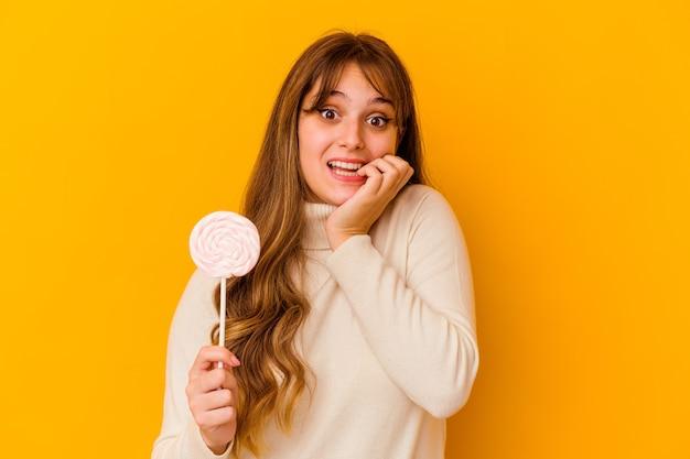 Giovane donna caucasica che tiene un lecca-lecca isolato su sfondo giallo unghie mordaci, nervose e molto ansiose.