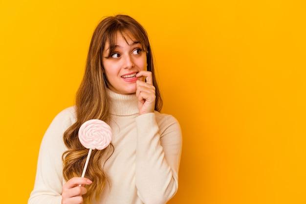 Giovane donna caucasica che tiene un lecca-lecca isolato