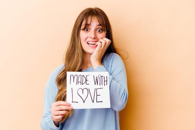 Giovane donna caucasica che tiene un fatto con le unghie mordaci isolate del cartello di amore, nervose e molto ansiose.