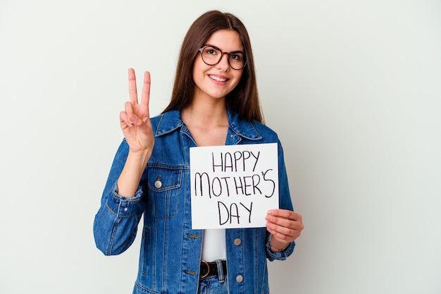 La giovane donna caucasica che tiene un fatto con il cartello di amore isolato sul muro bianco guarda da parte sorridente, allegro e piacevole.