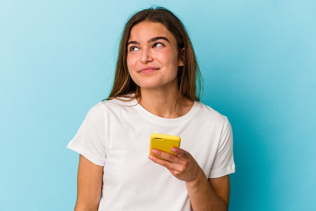 Giovane donna caucasica in possesso di un telefono cellulare isolato su sfondo blu che sogna di raggiungere obiettivi e scopi