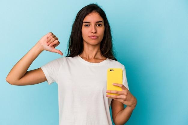 Giovane donna caucasica in possesso di un telefono cellulare isolato su sfondo blu che mostra un gesto di antipatia, pollice in giù. concetto di disaccordo.
