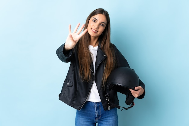 Giovane donna caucasica che tiene un casco del motociclo isolato sull'azzurro felice e contando quattro con le dita