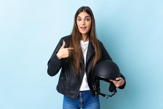 Giovane donna caucasica che tiene un casco del motociclo isolato sulla parete blu con l'espressione facciale di sorpresa