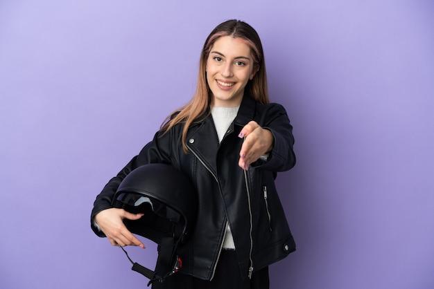 Giovane donna caucasica che tiene un casco del motociclo isolato sulla parete viola che stringe la mano per chiudere un buon affare