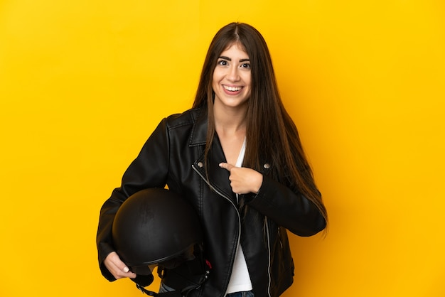 Giovane donna caucasica che tiene un casco del motociclo isolato sulla parete gialla con l'espressione facciale di sorpresa