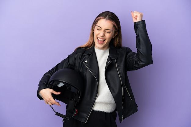 Giovane donna caucasica che tiene un casco del motociclo isolato