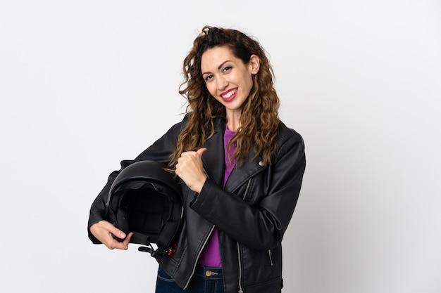 Giovane donna caucasica che tiene un casco del motociclo