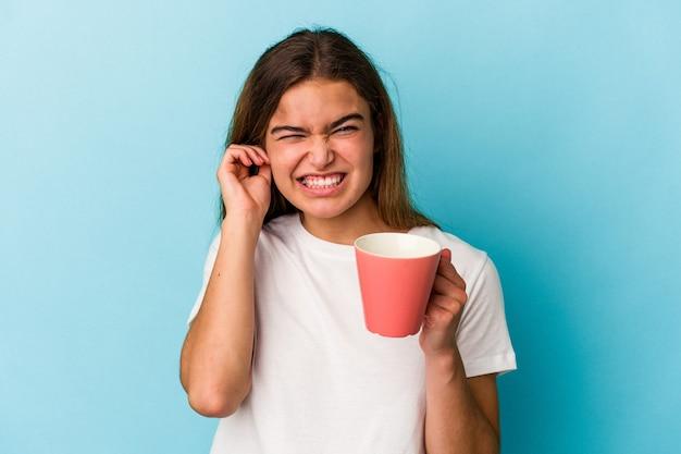 Giovane donna caucasica che tiene una tazza isolata su sfondo blu che copre le orecchie con le mani.