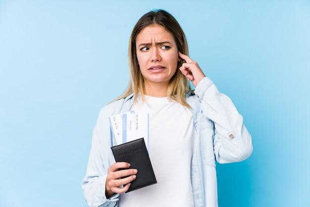 Giovane donna caucasica che tiene un passaporto isolato che copre le orecchie con le mani.