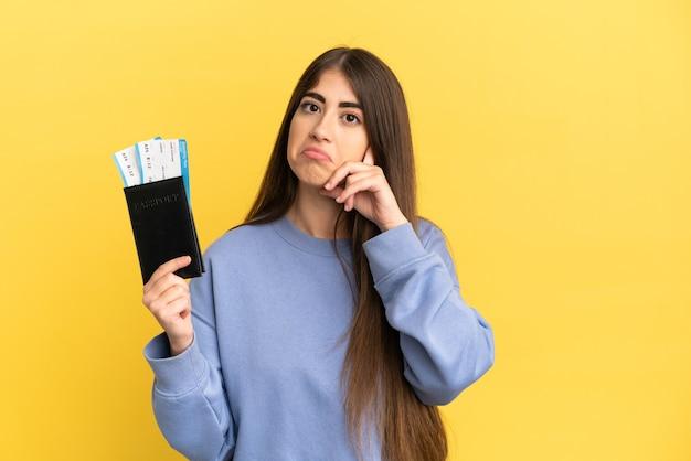 Giovane donna caucasica in possesso di un passaporto isolato su sfondo giallo pensando a un'idea