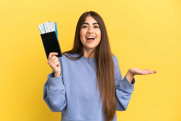 Giovane donna caucasica in possesso di un passaporto isolato su sfondo giallo con espressione facciale scioccata