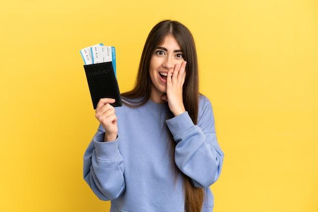 Giovane donna caucasica in possesso di un passaporto isolato su sfondo giallo con espressione facciale sorpresa e scioccata