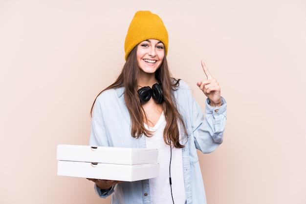 Pizze della holding della giovane donna caucasica isolate avendo un'idea, concetto di ispirazione.
