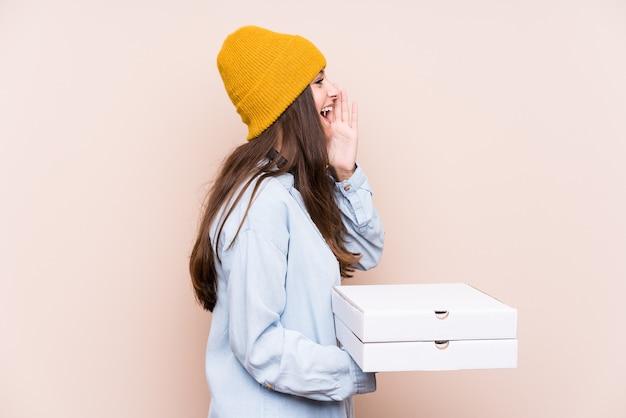La giovane donna caucasica che tiene le pizze ha isolato gridando e tenendo il palmo vicino alla bocca aperta.