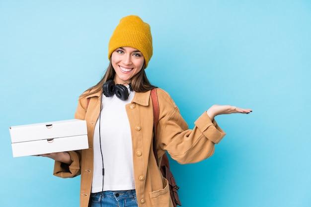 La giovane donna caucasica che tiene le pizze ha isolato mostrando uno spazio della copia su una palma e che tiene un'altra mano sulla vita.