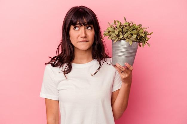 La giovane donna caucasica che tiene una pianta isolata sul muro rosa confusa, si sente dubbiosa e insicura.