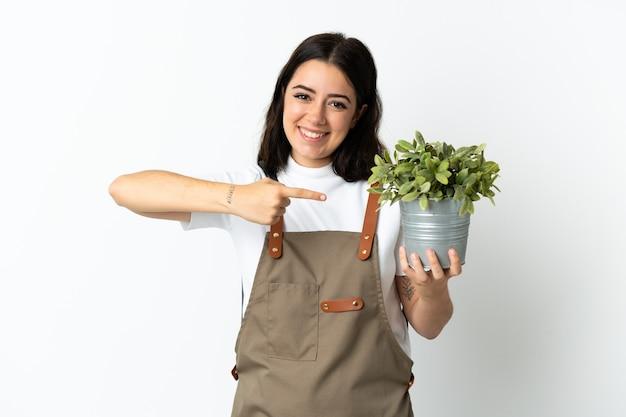Giovane donna caucasica che tiene una pianta isolata su fondo bianco e la indica